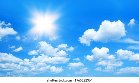 Sunny background, blue sky with white clouds and sun - Shutterstock ID 1765222364
