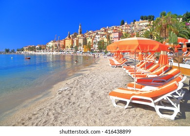 Sunny beach with chairs and umbrellas in Menton, French Riviera, France