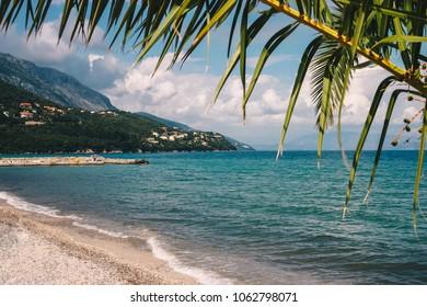 Sunny Beach of corfu island with palmleave framing the view.