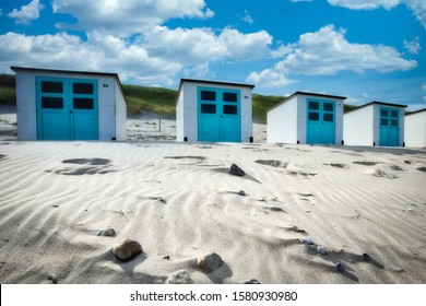 A sunny beach with dunes and beach houses a a summer day with white clouds and a blue sky in the background - Texel - The Netherlands