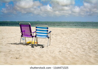 Sunny beach with some clouds sea sand and 2 deck chairs