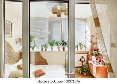 Sunny bedroom interior view through the balcony door