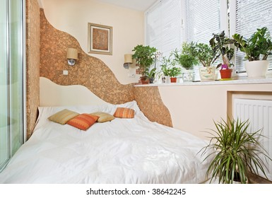 Sunny bedroom on balcony interior with Window and plants, wide angle view