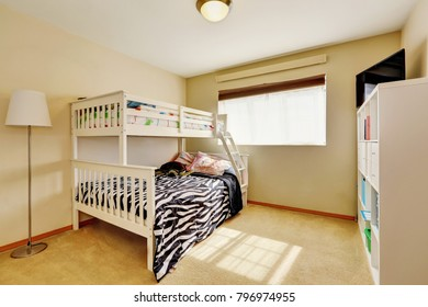 Sunny beige kids' room with a bunk bed with built-in ladder and dressed in zebra print bedding. Northwest, USA