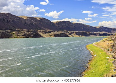 Sunny blue sky above a jade green lake along rocky cliffs in Eastern Washington desert.