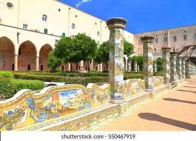 Sunny cloister of the Clarisses decorated with majolica tiles from Santa Chiara Monastery in Naples, Italy