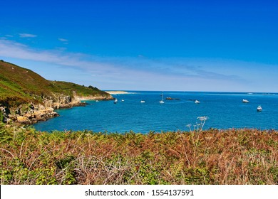 The sunny coastline of Herm. Belvoir bay and she'll beach with boats in the sales.