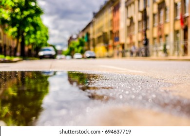 Sunny day after rain in the city, the empty road. Close up view from the level of the puddle on the pavement