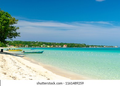 Sunny day along the Seven Mile Beach in tropical Negril, Jamaica. Tour boats await passengers and caucasian tourists in the water at a distance. Caribbean Jamaican summer beach vacation.