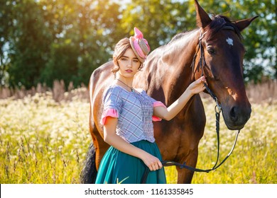 Sunny day beautiful woman standing next to the horse
