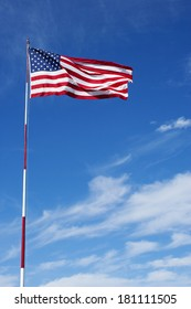 A sunny day, blue sky with some clouds with an American flag on a flag pole. Lots of open space for text.