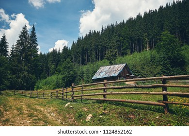 Sunny day in Carpathian mountains. Mountain road. Wooden fence.