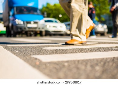 Sunny day in a city, pedestrians crossing the road. View from the level of asphalt