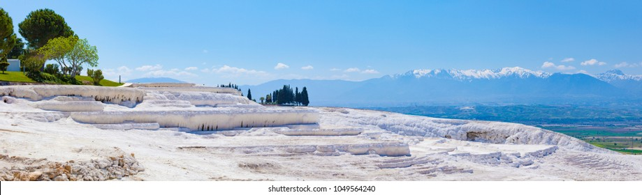 "Sunny day with clear blue sky in Pamukkale. Amazing white travertine, dry pool in Pamukkale, geological phenomenon, literally ""Cotton Castle"" in Turkish, most visited attraction in Turkey"