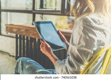 Sunny day. Close-up of tablet computer in hands of young woman sitting in room on chair.Hipster girl working online,blogging,chatting,checking email, watching video blog. Online marketing, education.