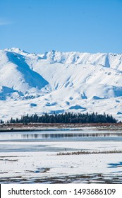 Sunny day during winter in New Zealand. Blue lakes, mountains, and snow. Lake Tekapo in the South Island.