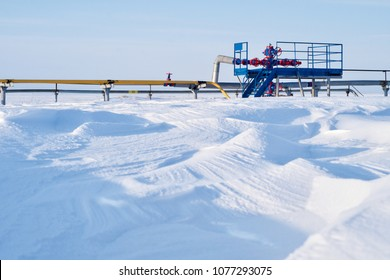 A sunny day, a gas well in the midst of a snowy field