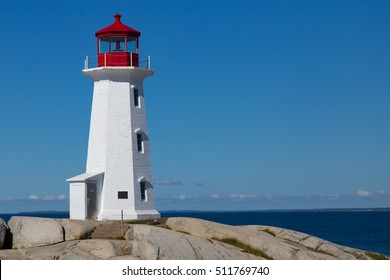 Sunny day at the iconic Peggy's Point Lighthouse, at the entrance to St. Margaret's Bay, on the  rocky shore of Peggy's Cove, Nova Scotia Canada
