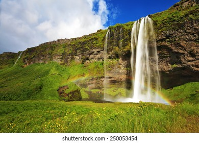 Sunny day in July. Seljalandsfoss waterfall in Iceland. Large rainbow decorates a drop of water