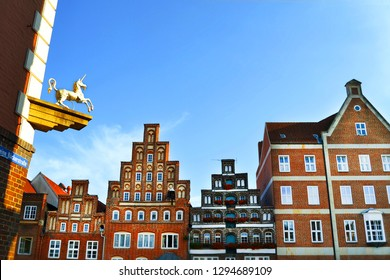 Sunny day in Luneburg, Germany, Europe. Brick gothic architecture and unicorn figurine on a building on Kleine bäckerstraße (small bakerstreet).