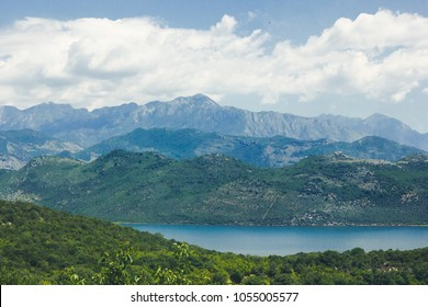 Sunny day mountain lake and blue cloudy sky scenic landscape background.