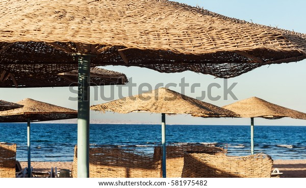 sunny day on the beach Straw umbrellas on sea background.