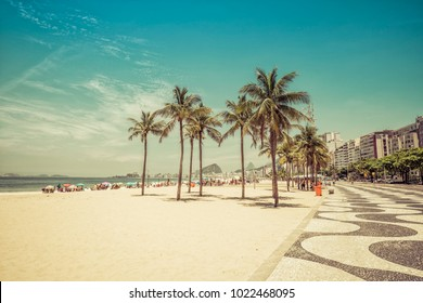 Sunny day on Copacabana Beach with palm trees in Rio de Janeiro, Brazil. Vintage colors