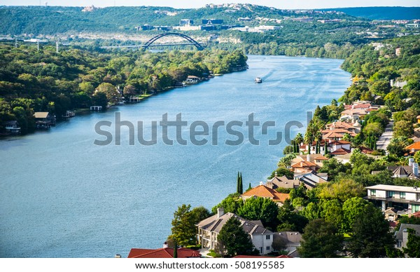 Sunny Day on Top of Mount Bonnell Overlooking Colorful Mansions on West Lake Austin Texas large Houses along Colorado River with Pennybacker Bridge in the Background