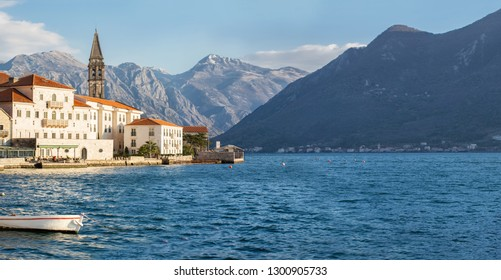 Sunny day on the waterfront in Perast Boka Bay, mountains in the background. Wide panorama