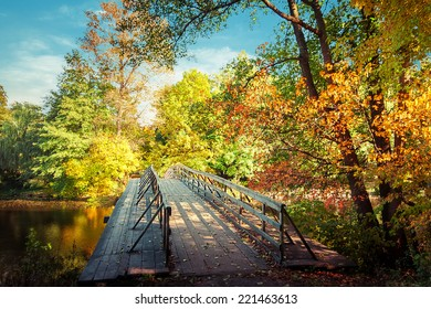 Sunny day in outdoor park with wooden bridge on lake and colorful autumn trees reflection under blue sky. Amazing bright colors of autumn nature landscape