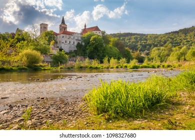 Sunny day in Sazava monastery with grass and river foreground, Czech Republic