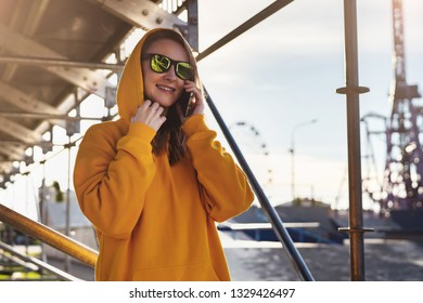 Sunny day. Smiling woman in yellow hoodie, in casual clothes talking on cell phone while standing outside. Girl in hood and sunglasses calls her friend on mobile phone while walking around city.