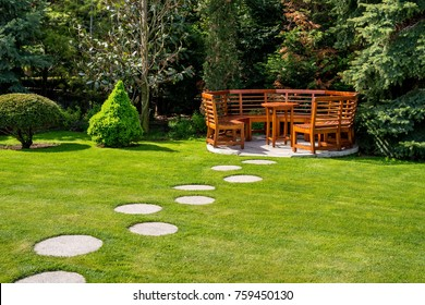 Sunny day in a spring garden with wooden table and benches - concept of lifestyle and leisure