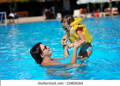 In the sunny day in the summer the boy in sun glasses and in a life jacket plays pool with mum