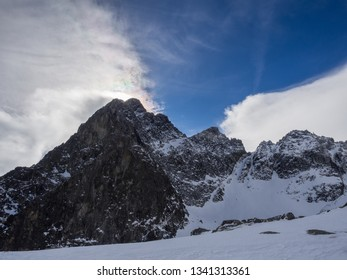 The sunny day view of Hight Tatras rocky mountain range with color spectrum in the clouds captured from Teryho Hut ( Téryho chata). High Tatras, Slovakia.