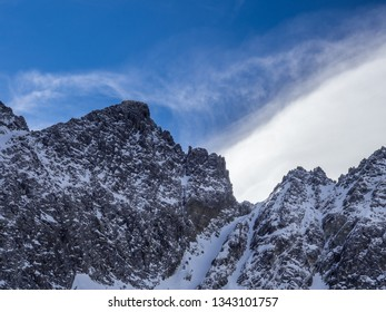 The sunny day view of Hight Tatras rocky mountain range with color spectrum in the clouds captured from Teryho Hut ( Téryho chata). High Tatras, Slovaka