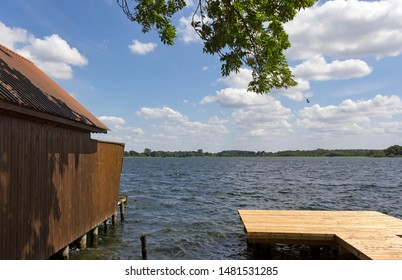 Sunny days, boathouse and pier at the lake Schaalsee, in front of a blue sky, Mecklenburg, Vorpommern.