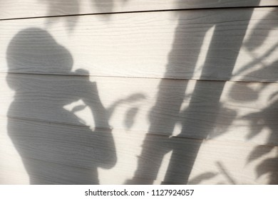Sunny evening background, shadow of people and leaf on white wall of the house, silhouette woman take photo lonely