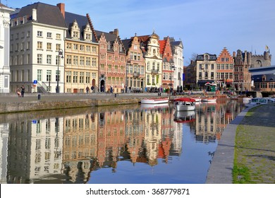 Sunny facades of old buildings reflected by the water in Ghent, Belgium