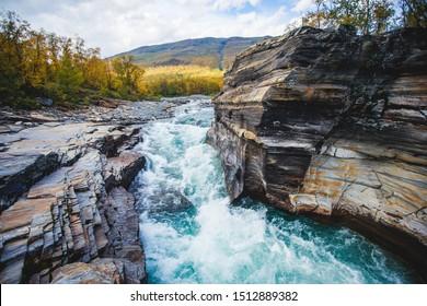 Sonniger Herbstblick auf den Abisko Nationalpark, Kiruna Stadt, Lappland, Norrbotten County, Schweden, mit Abiskojokk Fluss, Straße und Nuolja Berg, nahe der Grenze zu Finnland, Schweden und Norwegen