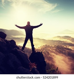 Sunny fall morning. Happy hiker with raised hands in air stand on rock above pine forest. View over misty and foggy morning valley to Sun.