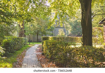 Sunny fall scenery in a park. A paved path with piles of orange leaves along it. A short green hedge following the path. A big tree on the right side. Old brick buildings in the distance
