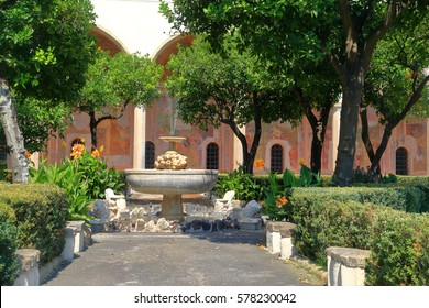 Sunny fountain surrounded by trees from the cloister of the Clarisses at Santa Chiara Monastery in Naples, Italy