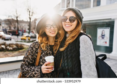 Sunny happy day of two joyful beautiful fashionable girls on street in city centre. Cheerful mood, friends, travelling together, walking with coffee to go, smiling, expressing positivity