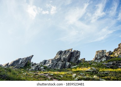 Sunny highland scenery with sharpened stones of unusual shape. Awesome scenic mountain landscape with big cracked pointed stones closeup among grass under blue sky in sunlight. Sharp rocks with cracks