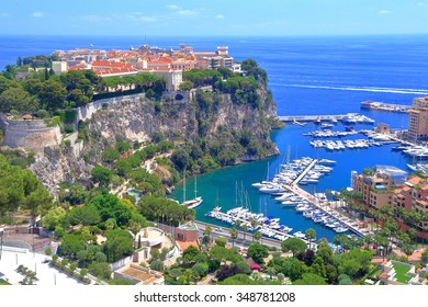 Sunny hillside with green vegetation above the marina of Fontvieille district, Monaco, French Riviera