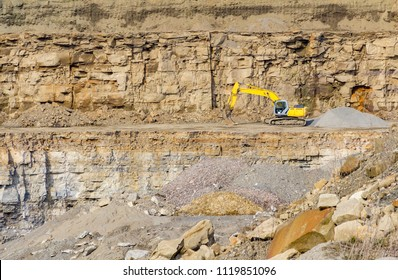 sunny illuminated stone pit scenery showing a rock formation with bucket excavator in Southern Germany