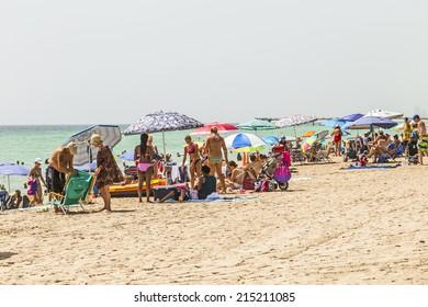 SUNNY ISLES BEACH, USA - AUG 17, 2014: people relax near the pier in Sunny Isles Beach, USA. In 1936, Milwaukee malt magnate Kurtis built the Sunny Isles beach and pier.