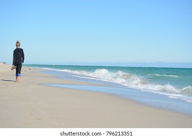 SUNNY ISLES BEACH, USA - DEC 9, 2017: Girl tourist walks barefoot along the beach of Sunny Isles, Florida