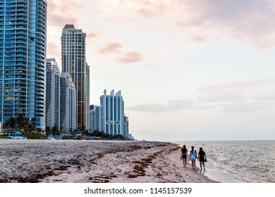 Sunny Isles Beach, USA - May 7, 2018: Apartment condo hotel buildings during vintage sunset evening in Miami, Florida with skyscrapers urban sand, waves crashing on shore coastline, people